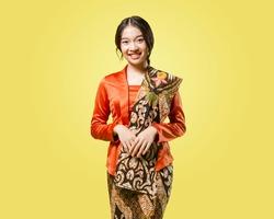Beautiful young indonesian woman wearing modern kebaya kutu baru with batik shawl isolated on yellow background