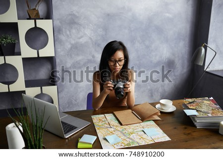 Beautiful young Korean female travel blogger sitting at home office with map, portable computer and diary, holding camera, choosing pics from road trip to upload them on her blog via social networks.