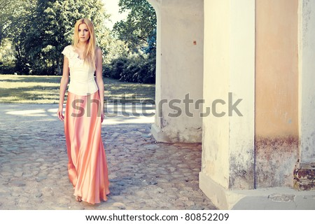 Beautiful young lady in long dress at old manor