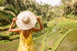 Beautiful young lady in shine through dress touch straw hat. Girl walk at typical Asian hillside with rice farming, mountain shape green cascade rice field terraces paddies. Ubud, Bali, Indonesia.