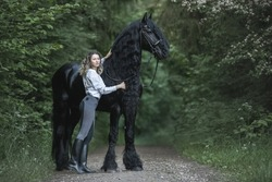Beautiful young lady posing with a purebred frisian horse in the summer forest.