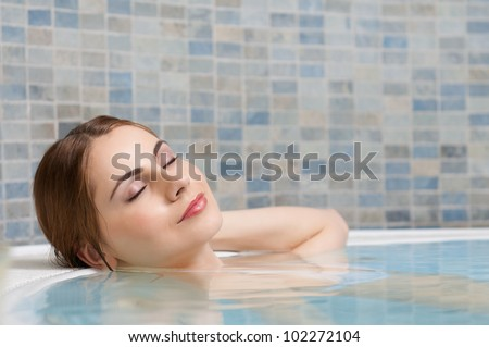 Beautiful young lady relaxing during a bath in a pool at thermal club
