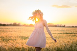 beautiful young lady walking in wheat fields during sunset, wear summer pink dress and  head flower wreath
