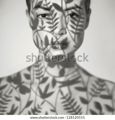 Beautiful young lady with a delicate floral pattern on face