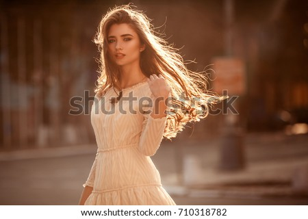 Beautiful young lady with long healthy hair and cute dress walking on the street. Hot summer evening. Sunset. Lifestyle concept.