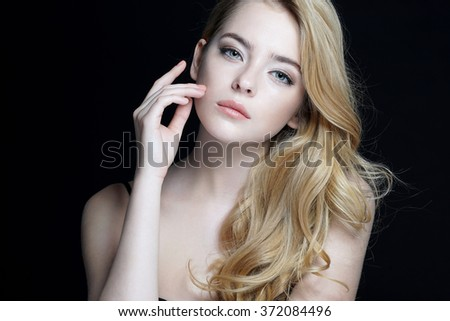 Beautiful young lady with make up face. Close-up of an attractive girl of European appearance on dark background. #372084496