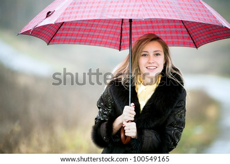 Beautiful young lady with red umbrella in rainy day isolated on autumn background