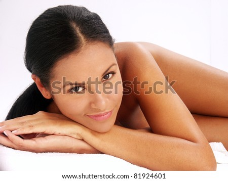 Beautiful young latin woman lying down on white background. Closeup portrait of young beautiful woman after bath - spa - stock photo