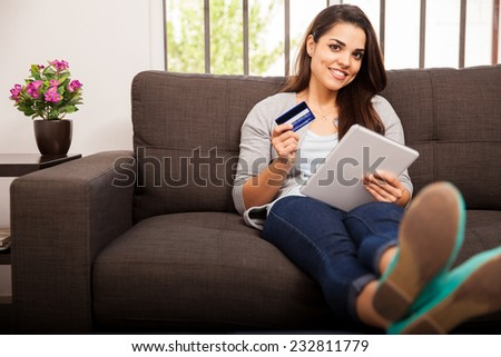 Beautiful young Latin woman using her credit card and tablet computer to purchase some stuff online
