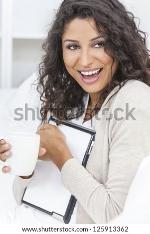 Beautiful young Latina Hispanic woman laughing, relaxing, using a tablet computer and drinking tea or coffee