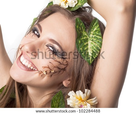 Beautiful young laughting woman with flowers, leaves in her hair and original make up