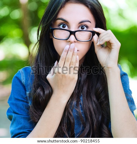 beautiful young long-haired woman glasses surprised covers mouth