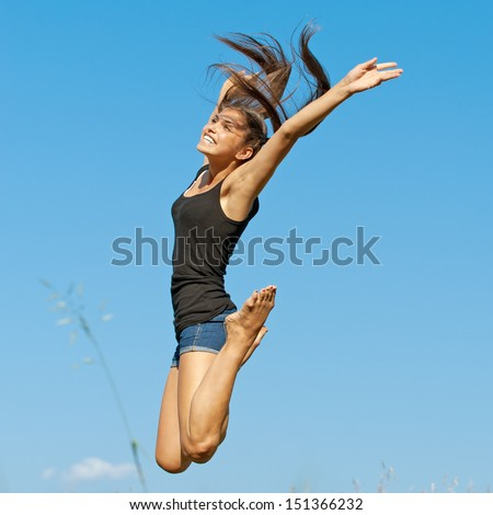 beautiful young long-haired woman jumping up background summer blue sky clouds
