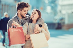 Beautiful young loving couple carrying shopping bags and enjoying together.