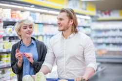 Beautiful young loving couple enjoying shopping discussing healthy lifestyle while walking along supermarket shelves together.
