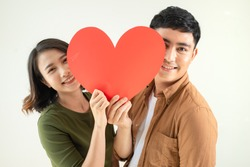 Beautiful young loving couple is holding a card in the shape of heart over white background.