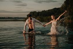 Beautiful young loving couple man and woman run near lake at sunrise. Holidays at sea on the beach, sunset, morning, honeymoon, tropics, ocean, girlfriend, relationship. Emotional relationships, fun.