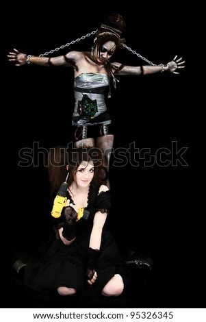 Beautiful Young Mad Scientist in gothic lolita dress with electric drill and her Cyborg Robot Prisoner Over Black.