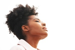 Beautiful young majestic black woman wearing a light pink jacket with a high puff updo hairstyle holds her head back against a white background outside with eyes closed