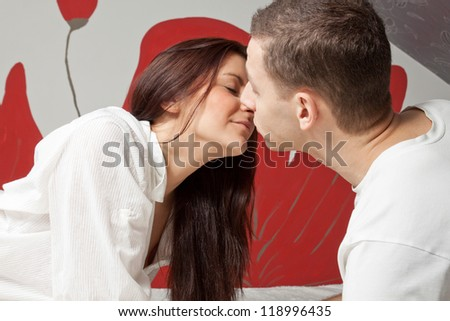 Beautiful young man and woman kissing in the bed