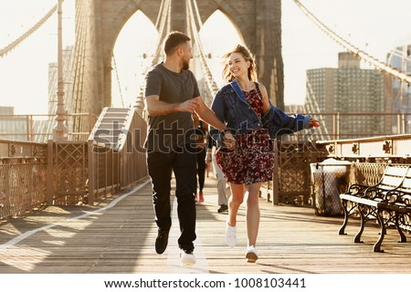 Beautiful young man and woman pose on the Brooklyn Bridge in the rays of morning sun #1008103441