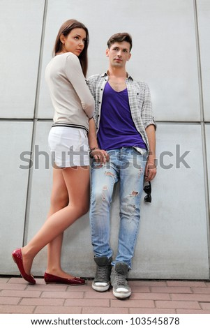 Beautiful young man and woman stand near gray wall and look not at camera