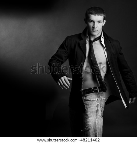 Beautiful young man posing on dark background - stock photo