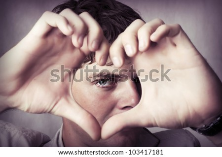 Beautiful young man show love sign