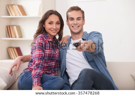 Beautiful young married couple is watching tv with joy. They are sitting on sofa and embracing. The man is holding the remote. They are smiling