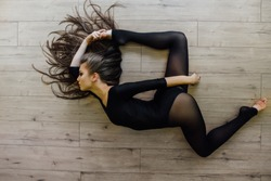 Beautiful young model ballet dancer lying on floor. Top view. working out at home studio, doing yoga exercise. Female, long curly brunette hair, a luxurious figure. dark tights and pantyhose.