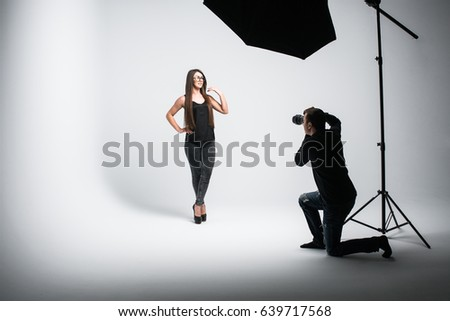 Beautiful young model is smiling and posing. the photographer is taking pictures with a digital camera