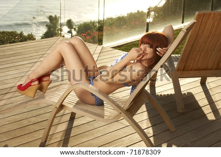 Beautiful young model with red hair wearing blue and white bikini sitting at lounge chair on patio of luxury California beach house on sunny day.