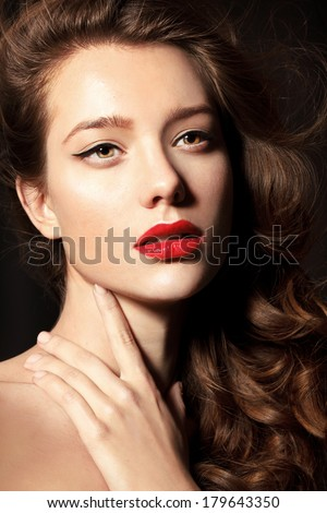 Beautiful young model with red lips and red manicure, shine hair