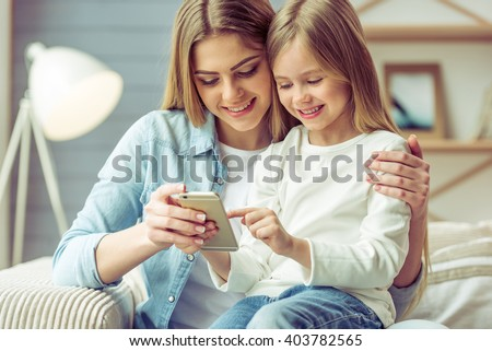 Beautiful young mom and her little daughter are using a smartphone and smiling while sitting on sofa at home #403782565