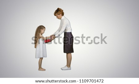 Beautiful young mom giving a present to her charming little girl on white background #1109701472