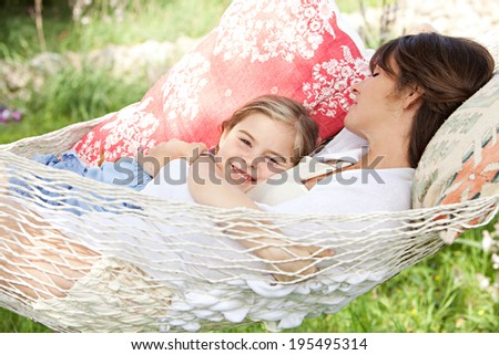 Beautiful young mother and daughter laying down and relaxing together on a hammock during a sunny summer day on holiday home garden. Family relaxing outdoors, healthy and wellness lifestyle.