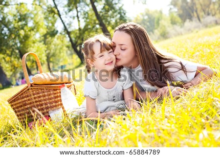 beautiful young mother and her daughter having picnic in the park on a sunny day