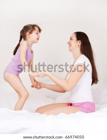beautiful young mother and her five year old daughter on the bed at home (focus on the mother)