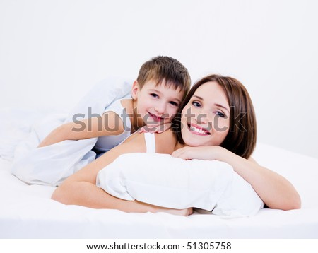 Beautiful young mother and son lying together on a bed