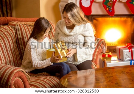 Stock Photo Beautiful young mother giving daughter present at Christmas eve