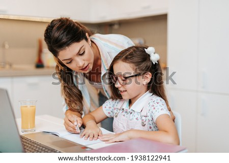 Beautiful young mother helping her younger daughter with homework. Foto stock ©