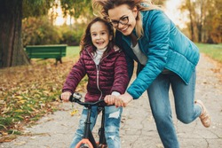 Beautiful young mother helping to her daughter to learn to ride a bicycle in the park. Cute little girl learning to ride a bicycle with her mother.
