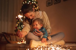 Beautiful young mother holding her son in her lap, sitting on the floor next to nicely decorated Christmas tree, playing with sparklers and christmas lights