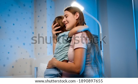 Beautiful young mother talking to her little toddler boy being scared of nightmare at night. Parent soothing and caressing child. Foto stock ©