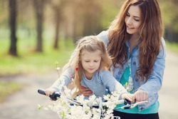 Beautiful young mother teaching her daughter to ride a bicycle. Both smiling, summer park in background, active family concept