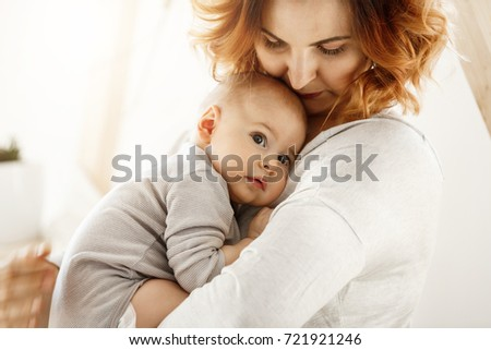 Beautiful young mother tenderly hugs her little cute child. Mom looking at her kid and smiling while baby looks aside and snuggling to mom chest. Happy family moments. #721921246