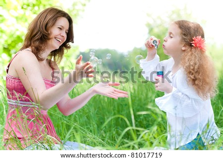 Beautiful young mother together with her daughter in nature making soap bubbles and laughing - stock photo