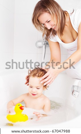 beautiful young mother washing her baby in the bath with foam (focus on the mother)