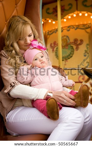Beautiful young mother with baby daughter taking a ride on traditional Parisian merry-go-round