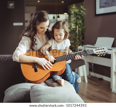 Beautiful young mother with her daughter together, learning playing musical instrument